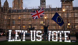 "© Licensed to London News Pictures. 27/03/2019. London, UK. Campaigning group Avaaz install 1.2 metre-tall illuminated letters spelling out ""LET US VOTE"" outside the Houses of Parliament. This evening MPs are expected to vote on a series of indicative votes on alternative proposals to British Prime Minister Theresa May's withdrawal agreement. Photo credit : Tom Nicholson/LNP"
