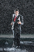 Businessman holding binder running in Rain