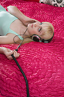 Teenage girl (16-17) lying on bed with headphones