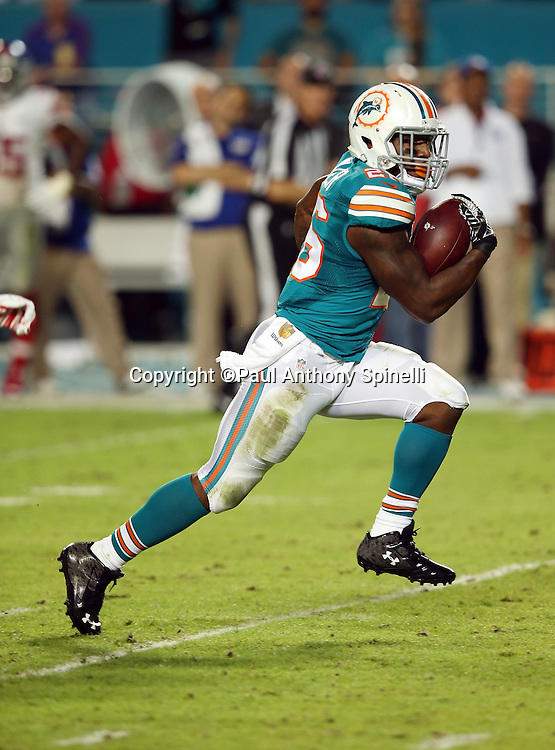 Miami Dolphins running back Lamar Miller (26) runs for a 38 yard second quarter touchdown good for a 14-10 Dolphins lead during the NFL week 14 regular season football game against the New York Giants on Monday, Dec. 14, 2015 in Miami Gardens, Fla. The Giants won the game 31-24. (©Paul Anthony Spinelli)