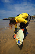 Surfer preparing his board on Fistral beach Newquay UK May 2002