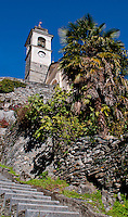 Stairs leading past a palm up to the church tower in Auressio in the Valle Onsernone in  Ticino, Southern Switzerland.