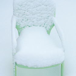 Green chair covered with fresh snow