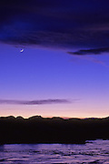 Crescent moon at twilight over the Rocky Mountain Front and frozen Nilan Reservoir. West of Augusta, Montana.