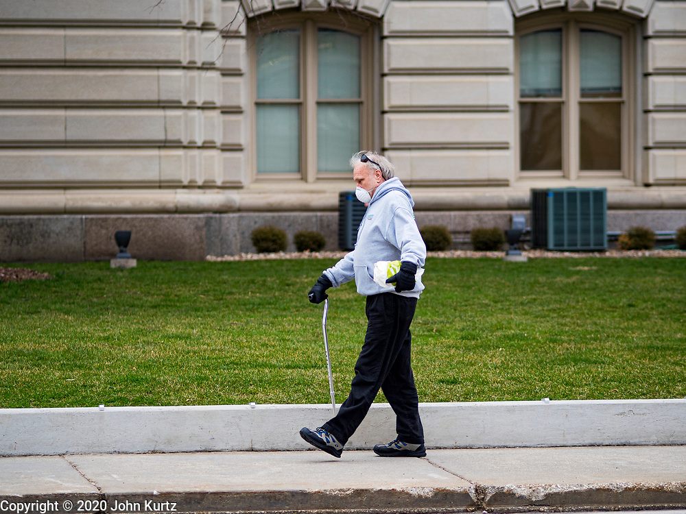 """24 MARCH 2020 - DES MOINES, IOWA: A person walks by the county courthouse in downtown Des Moines Tuesday. The city is deserted because many people are choosing to stay home and shelter in place because of the coronavirus. On Tuesday morning, 24 March, Iowa reported over 120 confirmed cases of the Coronavirus (SARS-CoV-2) and COVID-19. Restaurants, bars, movie theaters, places that draw crowds are closed for at least 30 days. The Governor has not ordered """"shelter in place""""  but several Mayors, including the Mayor of Des Moines, have asked residents to stay in their homes for all but the essential needs. People are being encouraged to practice """"social distancing"""" and many businesses are requiring or encouraging employees to telecommute.       PHOTO BY JACK KURTZ"""