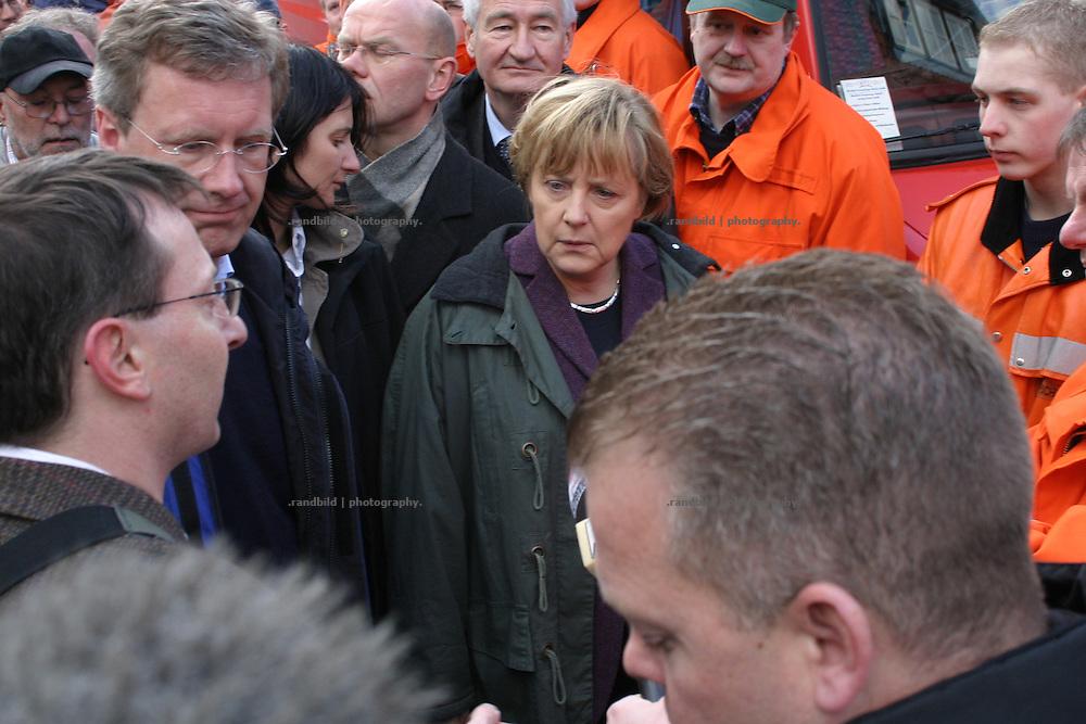Bundeskanzlerin Angela Merkel (CDU) blickt betroffen bei einem Besuch der überfluteten Altstadt in Hitzacker