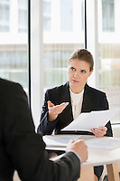Businesswoman discussing over documents with colleague in office cafe