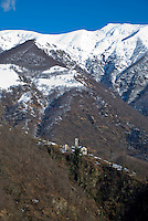 Ticino, Southern Switzerland. Snow-capped mountains towering over a small church in the Italian Alps.