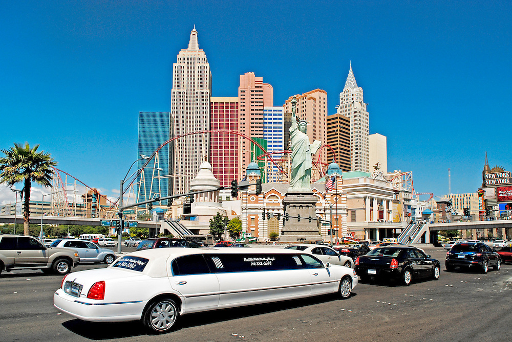 """USA, Nevada, Las Vegas, Traffic with a white limousine  - sedan - in front of the Hotel and  casion """"New York"""". The hotel complex re-creates Manhattan skyline with 12 New York style skyscrapers, a 529 ft Empire Statue Building, a 150 ft Statue of Liberty, a 300 ft long Brooklyn Bridge and a Coney Island style rollercoaster called the Manhattan Express. The hotel has 2,034 rooms.