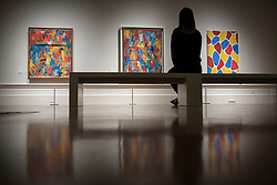 """© Licensed to London News Pictures. 19/09/2017. London, UK. A visitor views (L to R) """"Painting With Two Balls"""", 1960, """"False Start"""", 1959, and """"Nines"""", 2006, all by Jasper Johns.  Preview of a landmark exhibition by Jasper Johns RA called """"Something Resembling Truth"""" at the Royal Academy of Arts in Piccadilly.  Sculptures, drawing, prints plus new works are on display 25 September to 10 December 2017.   Photo credit : Stephen Chung/LNP"""