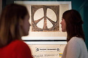 UNITED KINGDOM, London: 21 March 2017 Members of staff at The Imperial War Museum stand in front of an original sketch of the world famous nuclear disarmament symbol by designer Gerald Holtom. It forms part of the 'People Power: Fighting for Peace' exhibition at the Imperial War Museum which explores the evolution of the anti-war movement from the First World War to the present day. Rick Findler / Story Picture Agency