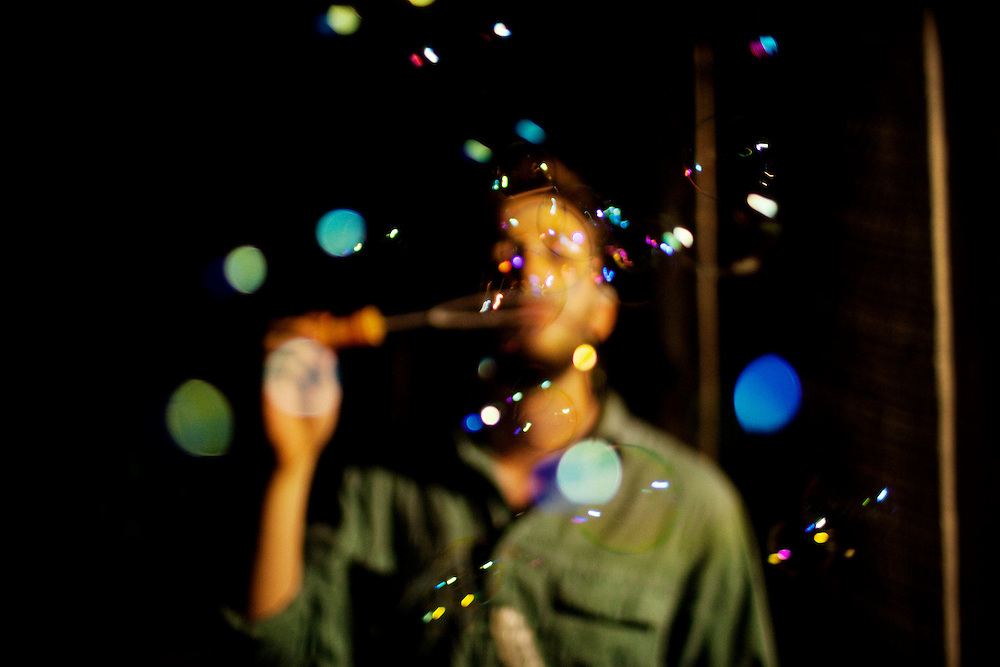 Noah Rabinowitz blows bubbles late at night while hanging out with friends at his cabin in the woods in Athens, Ohio.