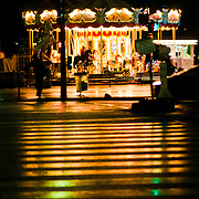Lights of one of the carousels near the Eiffel Tower reflect on a damp zebra pedestrian crossing.