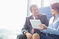 Businessman and businesswoman using tablet PC in office