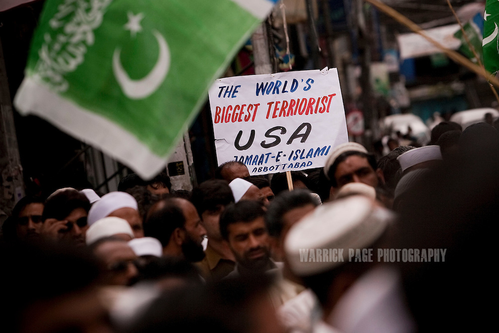 A Pakistani man holds an anti-US poster at a demonstration by members of Jammat-i-Islami protesting the killing of Osama Bin Laden by US forces, on 6 May, 2011, in Abbottabad, Pakistan.  The operation, code-named Operation Neptune Spear, was launched from neighbouring Afghanistan by Seal Team Six. U.S. forces took bin Laden's body to Afghanistan for identification, then dumped it the Arabian Sea. Pakistan has since been widely suspected as having prior knowledge of his whereabouts as the compound was less than a kilometre from the country's biggest military academy. Osama bin Laden was allegedly responsible for supporting the bombing of the US Embassy in Nairobi, Kenya, the attack on the USS Cole and the suicidal attacks of September 11, 2001 in the US. (Photo by Warrick Page)