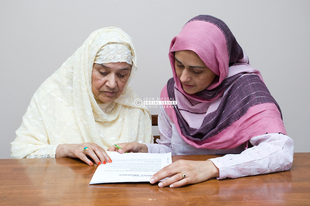 Young female carer helping older woman fill out a tax allowance form,