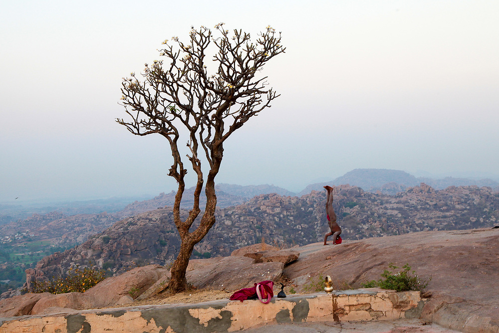 Indian Sannyasi  praticing Yoga before sunrise on top of Anjanadri Hill near Hampi, India. <br />
