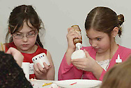 Kayla Coffman, 9 (left) and  Tara Nix, 8, from Waynesville add artistic touches to candles at the American Girl Tea Party, Saturday, January 27, 2007 in Waynesville's Mary L. Cook Library.  They got to take the candles home at the end of the party.