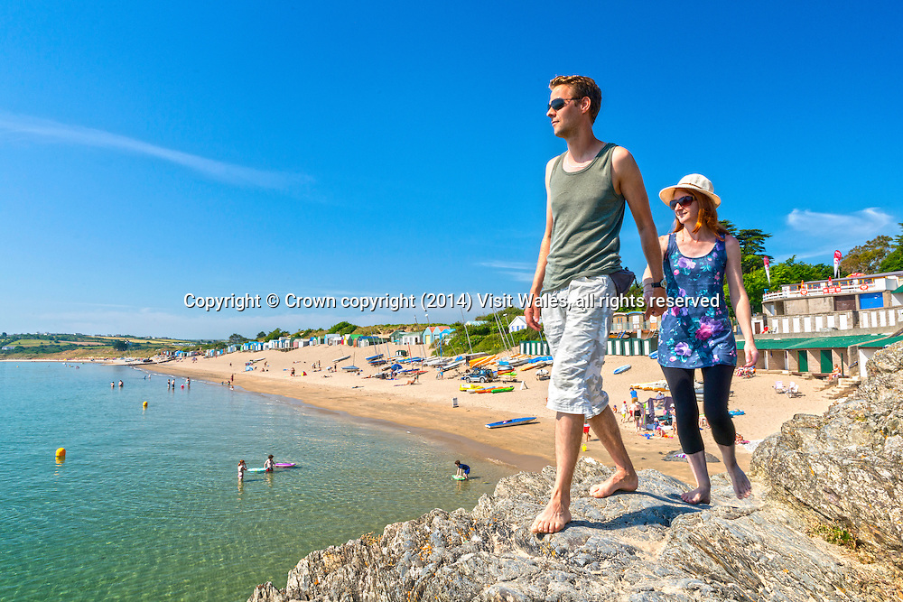 Couple walking along rocks with beach in background<br /> Abersoch<br /> Llŷn Peninsula<br /> Gwynedd<br /> North<br /> Towns and Villages<br /> People<br /> Lifestyle