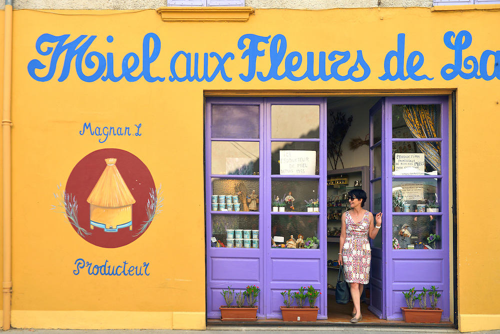Woman stepping out of shop, Valensole,Provence,Frqance<br /> Model release 0350