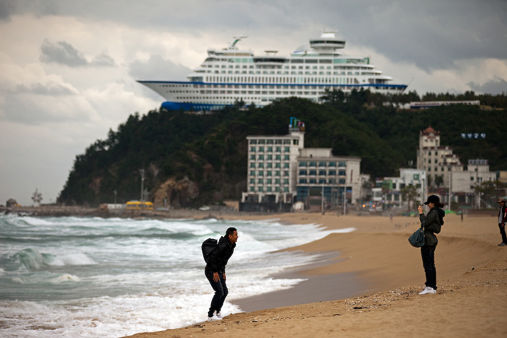 Young Korean couple photographing themself on the beach, in the background the giant cruise ship on a hilltop - Suncruise resort / Jeongdongjin, South Korea, Republic of Korea, KOR, 07 October 2009.