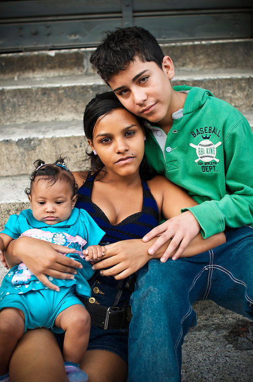 Teenage parents, Diovile Toro, 18, and her boyfriend, Gilberto Marquez, 16, pose for a portrait with their 5-month old daugther, Diovelys.  Toro and Marquez live together in a slum in Caracas, Venezuela supported by Marquez's construction job.
