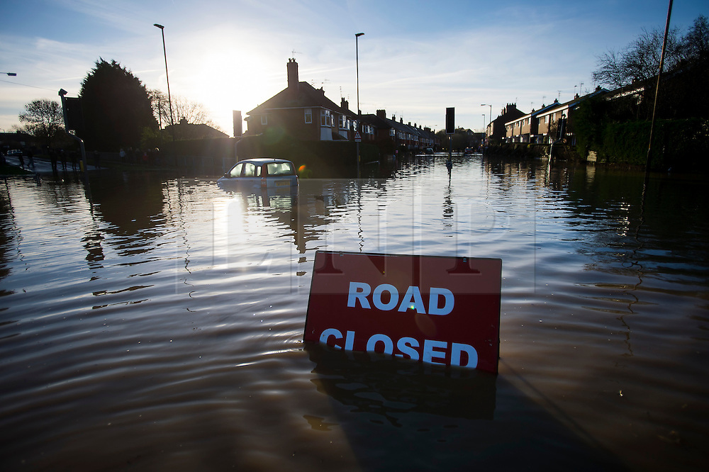 © Licensed to London News Pictures. 27/12/2015. York, UK.  A road closed sign and a car submersed in flood water on Huntingdon Road in York. Large areas of the North of England have been hit by severe flooding following unusually heavy rainfall in December. Photo credit: Ben Cawthra/LNP