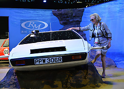 "© Licensed to London News Pictures. 08/09/2013. London, England. RM Auctions Classic Car auction at Battersea Evolution, London. Photo credit : Mike King/LNP. RM Auctions 8-9 September 2013 at Battersea Evolution. A car enthusiast named Johanna poseswith the 007 Lotus Esprit ""sumarine car"". It is offered without reserve, but expected to sell for £650,000-£950,000."