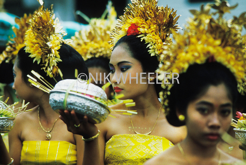 Young women in traditional costume at purifaction ceremony at Kuta Beach in Bali, Indonesia.