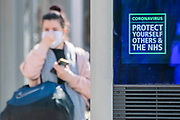 A BT InLinkUK digital sign displays NHS Coronavirus information as members of the public go about shopping for food and for mother's day - Anti Coronavirus (Covid 19) outbreak in London.