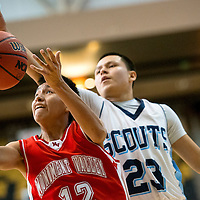 120513   Brian LEddy<br /> Monument Valley Mustang Brayton Begay (12) drives towards the hoop as Window Rock Scout Latrell Kaye (23) reaches for the ball during Thursday's Coca Cola Classic in Chinle. The Mustangs won 60-56.