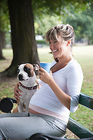 Pregnant woman on park bench with dog