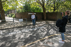 """© Licensed to London News Pictures. 16/09/2018. London, UK. Tourists pose next to community activists spray paint """"Drug Dealer Only"""" parking spaces and erect street signs to highlight increasing levels of drug dealing in the E2 postcode, known as the cheapest heroin in Europe, East London, UK. Photo credit: Ray Tang/LNP"""