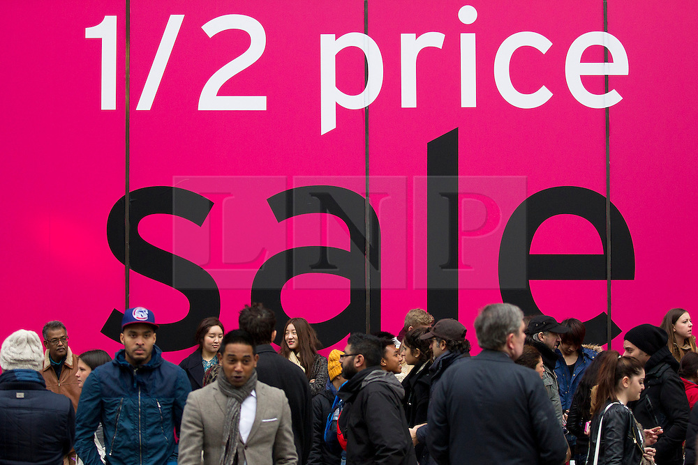 © Licensed to London News Pictures. 26/12/2013. London, UK. Shoppers search pass a sale sign at Topshop on Oxford Street as they search for bargains during the Boxing Day sales in London today (26/12/2013). Photo credit: Matt Cetti-Roberts/LNP