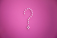 Close-up of push pins forming question mark over pink background
