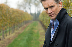 Mature man standing in a grapevine field