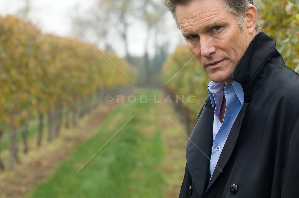 Mature man standing in a grapevine field