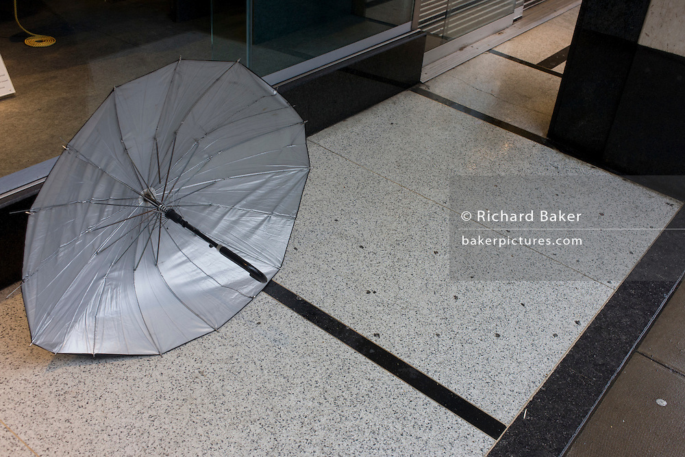 Detail of an abandoned umbrella left outside a central London shop and the continuation of a black line.