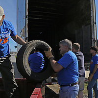Aaron Stewart | BUY AT PHOTOS.DJOURNAL.COM<br /> Cooper Tire employees Brian Weibel and Ahmad Elmaghraby work to unload tires out of the bed of a truck as part of the company's Tire Recyling Day on Saturday morning.