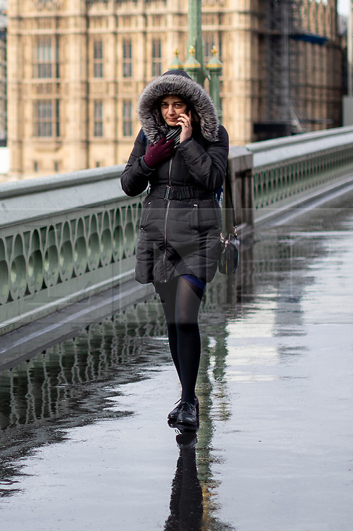 © Licensed to London News Pictures. 04/04/2019. London, UK. A woman walks across Westminster Bridge as heavy rain falls in Westminster. Photo credit : Tom Nicholson/LNP
