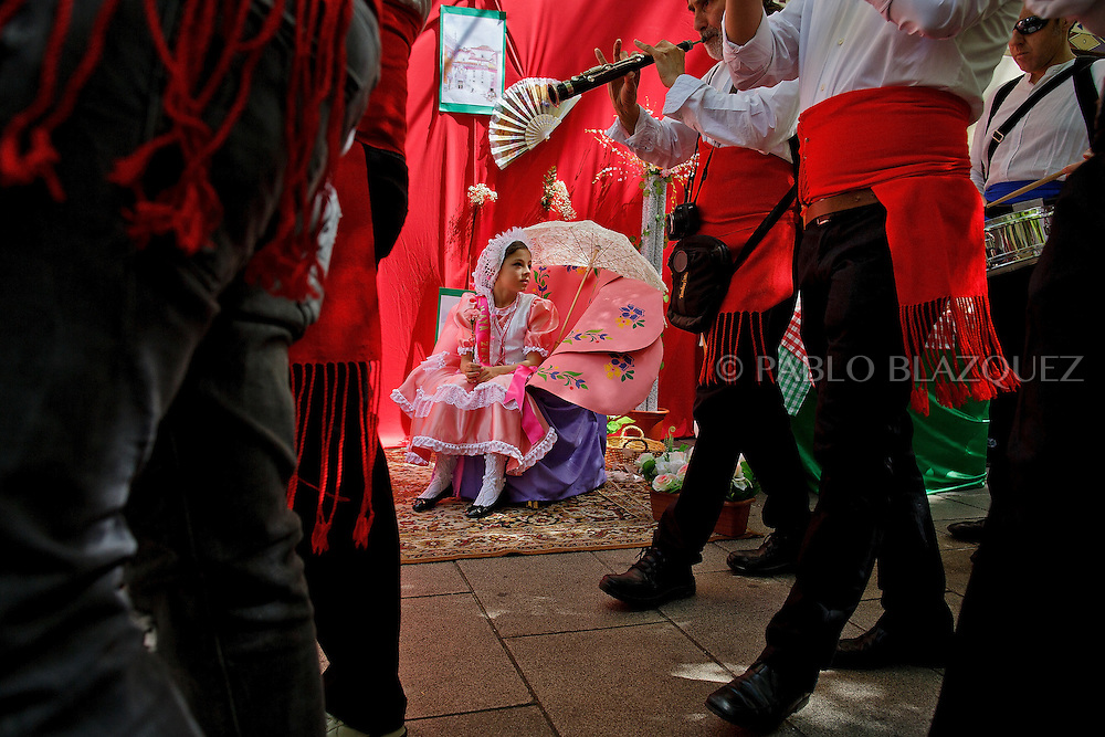A 'Maya' girl sits on the altar during the 'La Maya' tradition as a music band parade passes by along the street near the San Lorenzo church on May 10, 2015 in Lavapies neighborhood, Madrid, Spain. 'La Maya' festivity is a pagan tradition to celebrate the beginning of the spring which is believed to come from the medieval age. In old times the 'Maya's Festival' used to take place at The 'Mayas' field' (Prado de las Mayas) which is where now the San Lorenzo church is located. La Maya combines symbols of fertility and prosperity on agriculture and shepherding economy. A 'Maya' girl dressed with traditional customs sits on an altar in the street decorated with flowers, plants and cushions. Other Mayas and Mayos offer flowers, traditional sweets, lemonade, and wine to members of the public as they play music and dance. (© Pablo Blazquez)