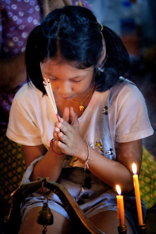 A young woman prays at New Years Eve morning celebrations at a temple in rural Thailand.