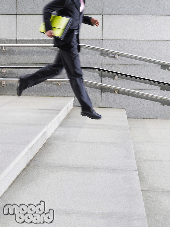 Business man running down steps outdoors side view low section