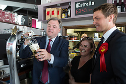 © Licensed to London News Pictures . 11/04/2015 . Bury , UK . Labour Shadow Chancellor ED BALLS (l) pours a pint . Ed Balls and James Frith (r) , Labour candidate for Bury North , at a campaign stop with the owner of Barista coffee shop (c) at The Rock , Bury in Greater Manchester , UK . The pair met parents and discussed family finances . Photo credit : Joel Goodman/LNP