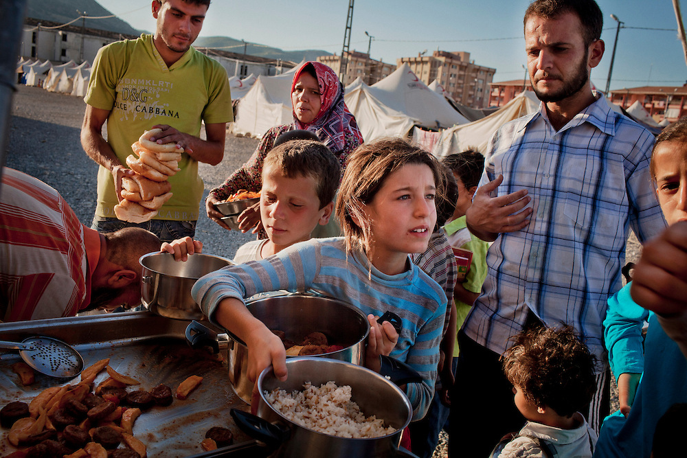 Syrian refugees receive their family meal in Islahiye refugee camp, where around 6000 refugees are living. Southern Turkey few km north of the Syrian border. July 15, 2012. Photo/Tomas Munita