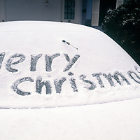 Merry Christmas written in the snow on a car windshield