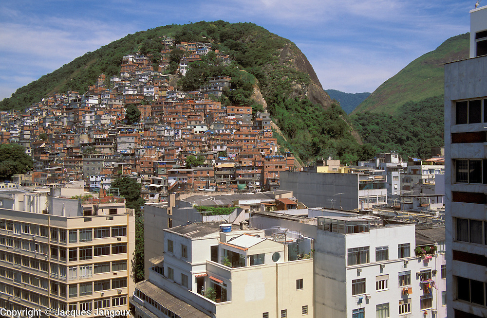 Contrast between middle class buildings in Copacabana in foreground and slum callled favela in Brazil on Morro do Pavao hill , Rio de Janeiro, Brazil.