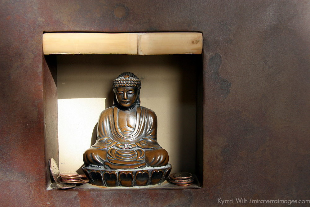 Detail of a Buddha with coins in a nook at Ten Thousand Waves, luxury resort spa in Santa Fe, New Mexico.