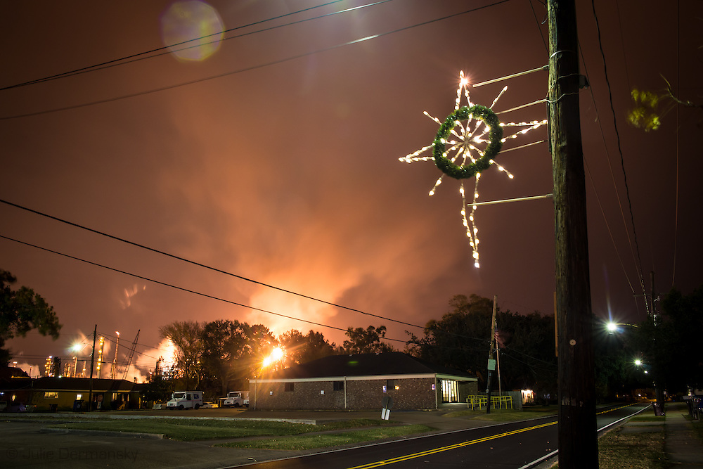 """December 19th, 2013, Norco Louisiana, A flare from the Shell Refinery shines along with Christmas lights on residents homes. Norco is part of a corridor between Baton Rouge and New Orleans known to those in Industry and the 'petrochemical corridor' and to locals as """"cancer alley"""". '"""