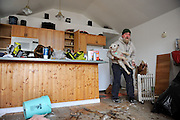 Kevin Cox lifts his dog Griizzly off the dirty floor of his water-logged home in Broad Channel, Queens, Nov. 3., 2012.